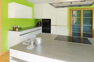 Küche mit Edelstahlabdeckung, weiss lackierten Fronten und Griffleisten
