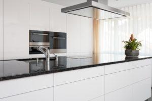 Küche von Kläger - Front weiss hochglanz lackiert mit dunkler Granit Arbeitsplatte