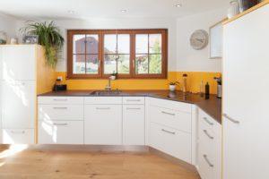 Küche von Kläger - satinierte Glasrückwand orange lackiert und Keramik Arbeitsfläche in Neolith Iron Copper